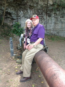 Bill Schott and Laura Leppert, President of Daughters of World War II, and Bill sitting on the remains of a cannon during the 68th Anniversary of Iwo Jima