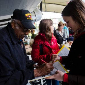 WWII veteran Ormond Knowles, signs autographs for Belgian high school students during a visit to a WWII museum in France.
